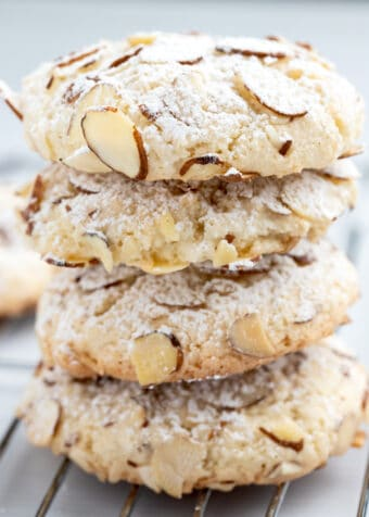 Side view of almond paste cookies stacked on top of each other with sliced almonds and powdered sugar