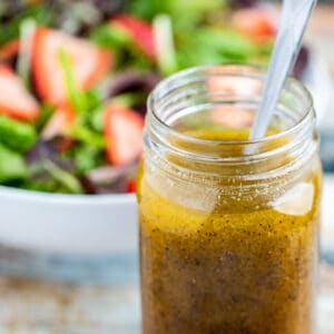 Side view of mason jar full of poppy seed dressing with spoon and strawberry salad in the background