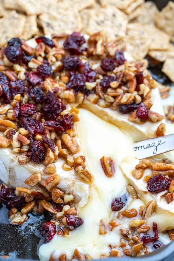top view on pecan cranberry baked brie with melted cheese flowing out and surrounded by crackers