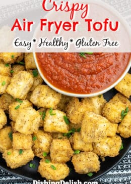 Pinterest pin with title box on top. Overhead photo of air fried golden brown tofu cubes on a plate next to a bowl of marinara dipping sauce.