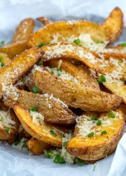 side view shot of air fryer potato wedges topped with parmesan and chopped chives
