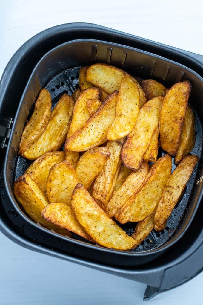 Overhead shot of air fryer basket full of crispy cooked potato wedges