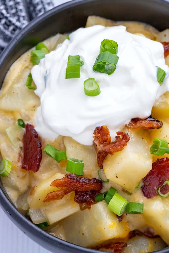 Top down view of a black bowl full of baked potato casserole topped with bacon, green onions, and sour cream.
