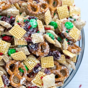 downward view of bowl with christmas chex mix made of pretzels, chex cereal, M&Ms, and dried cranberries coated in white chocolate